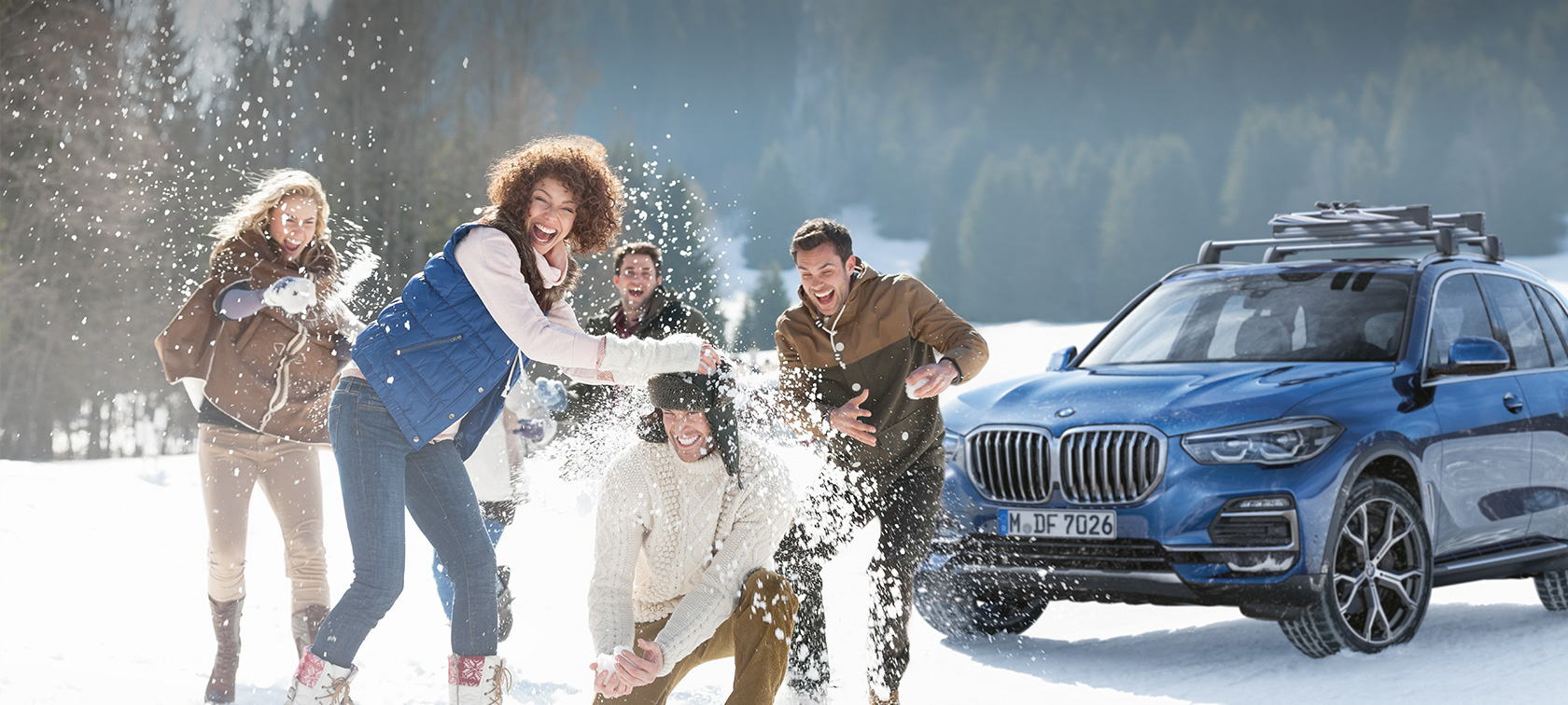 Women and men laughing in the snow in front of a BMW